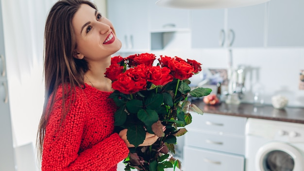 Valentines day. young woman found bouquet of red roses on kitchen. happy girl holding flowers. Premium Photo
