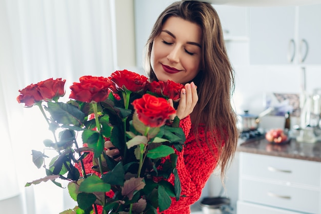 Valentines day. young woman found bouquet of red roses on kitchen. happy girl holding and smelling flowers. Premium Photo