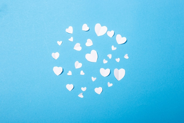 Valentines made of paper in the shape of a heart on a blue background. composition of valentine's day. banner. flat lay, top view. Premium Photo