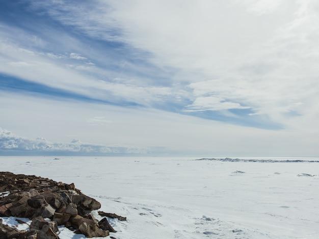 Долина покрыта снегом в холодный зимний день под ярким облачным небом Бесплатные Фотографии