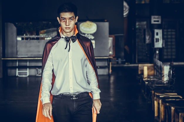 黒のハロウィーンの衣装で血を持つ吸血鬼男。ハロウィーンの概念。 Premium写真