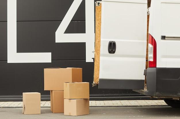 Фургон с открытой дверью и картонными коробками на земле это доставка груза Premium Фотографии