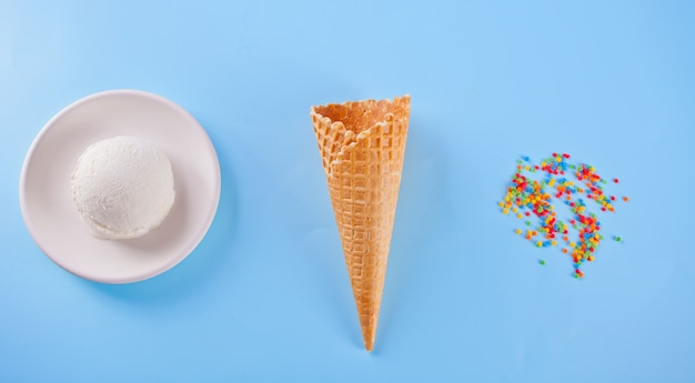 Vanilla ice cream with waffle cones and candy on the blue background Premium Photo