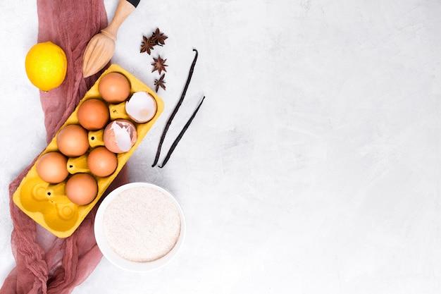 Vanilla pod; eggs; lemon; star anise; flour and wooden squeezer on white textured background Free Photo