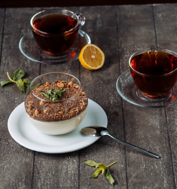 Vanilla pudding covered with chocolate crumbs and nuts, served with tea Free Photo