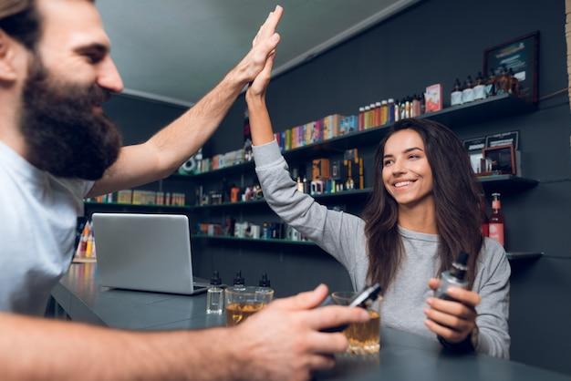 Мужчина и женщина с электронной сигаретой в vapeshop. Premium Фотографии