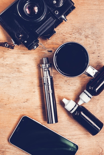 Vaping set, vintage camera, smartphone and coffee on the wood table Premium Photo