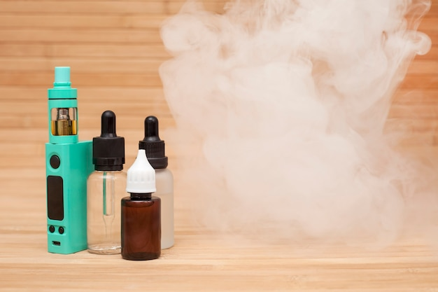 Vaping set on the wooden table with vapor. Premium Photo