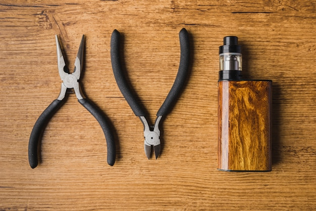 Vaping tools with wood background and mod Premium Photo