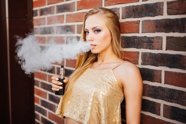 Vaping. young beautiful woman smoking e-cigarette with smoke outdoors. vapor concept. Free Photo