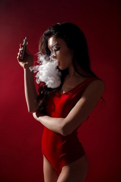 若いセクシーな女性がvapingです。蒸気の雲。 Premium写真