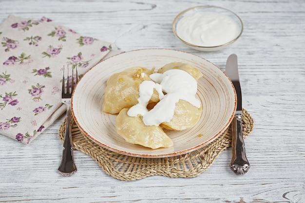 Vareniki with onion and sour cream Premium Photo
