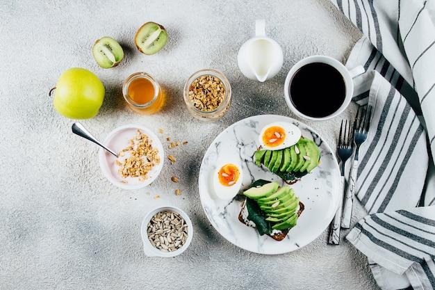 Variation of full breakfast. avocado toasts, eggs, yogurt with granola, fruits, seeds, black coffee Premium Photo
