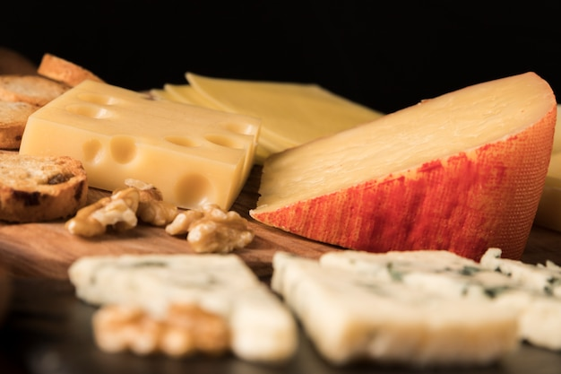 Variation of tasty cheeses on wooden table Free Photo