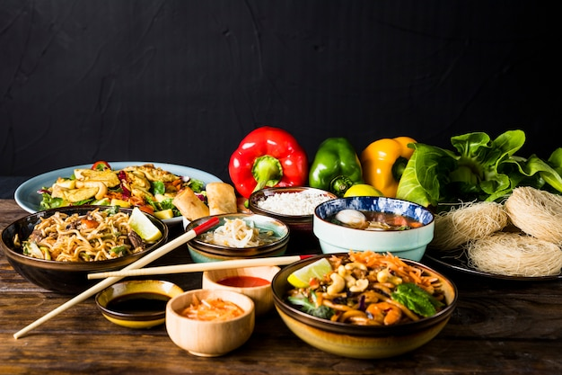 Variation of thai cuisine with bell peppers and bokchoy on wooden desk against black background Free Photo