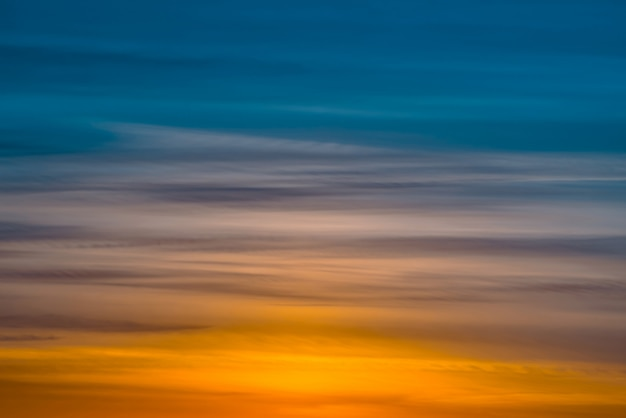 Varicolored striped dawn sky with shades of blue, cyan, cobalt, pink, purple, magenta colors. horizontal lines of picturesque clouds. atmospheric background image of warm sky Premium Photo