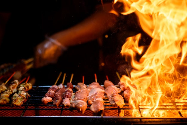 Variety of barbecue skewers meat kebabs with vegetables on hot flaming grill Premium Photo