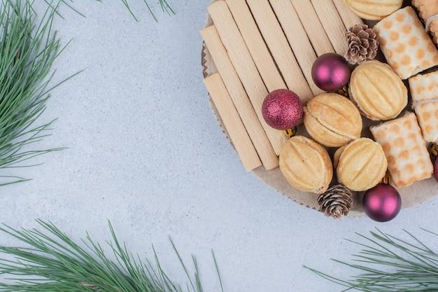 Varietà di biscotti e addobbi natalizi su tavola di legno. Foto Gratuite