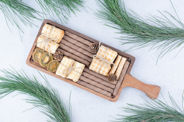 Variety of biscuits and dried kiwi on wooden board. Free Photo