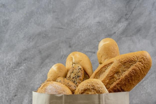 Разнообразный хлеб в одноразовом бумажном пакете. пекарня, еда и напитки, и концепция бакалеи для доставки. Premium Фотографии