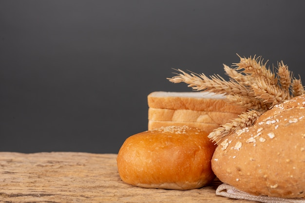 Variety of bread on wooden table on an old wooden background. Free Photo