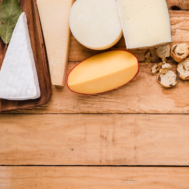 Variety of cheeses ; bread and walnut on table with space for text Free Photo