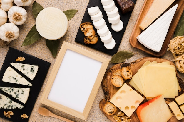 Variety of cheeses and healthy ingredients with blank white picture frame over textured backdrop Free Photo