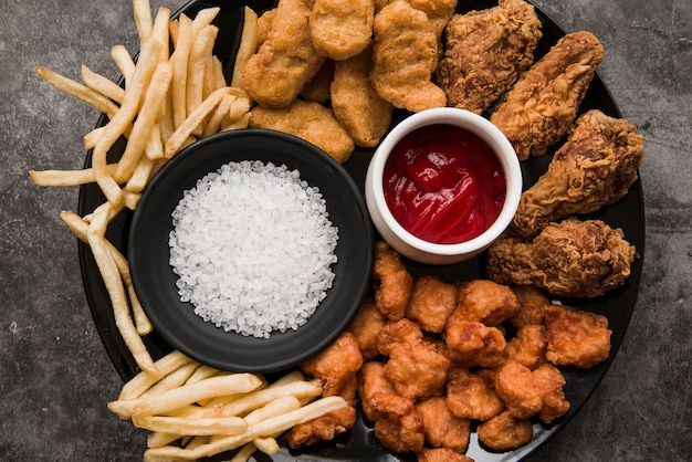 Variety of chicken dishes; french fries with salt and tomato sauce in plate Free Photo