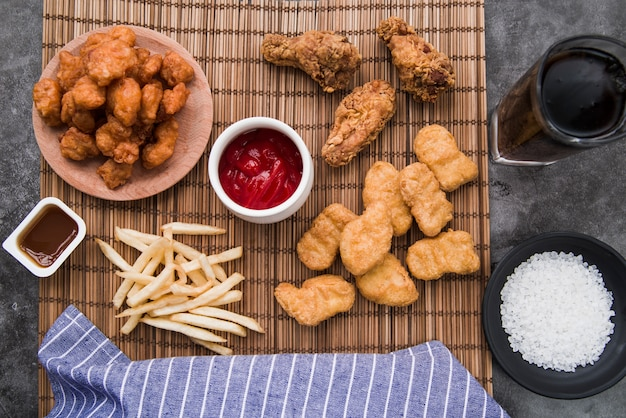 Variety of chicken foods with french fries and soft drink on bamboo mat Free Photo