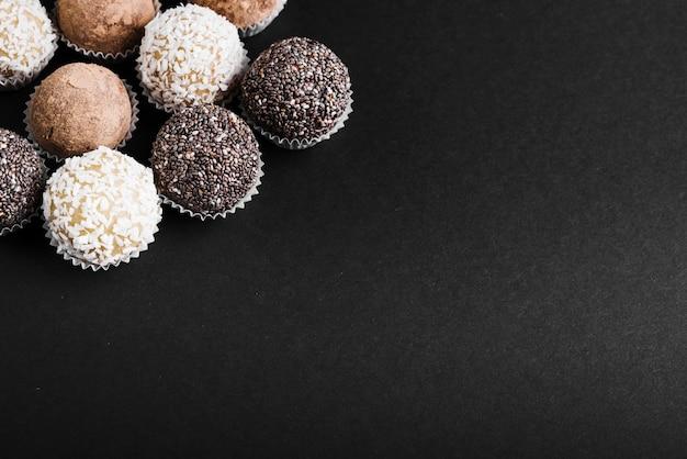 Variety of chocolate balls on black background Free Photo