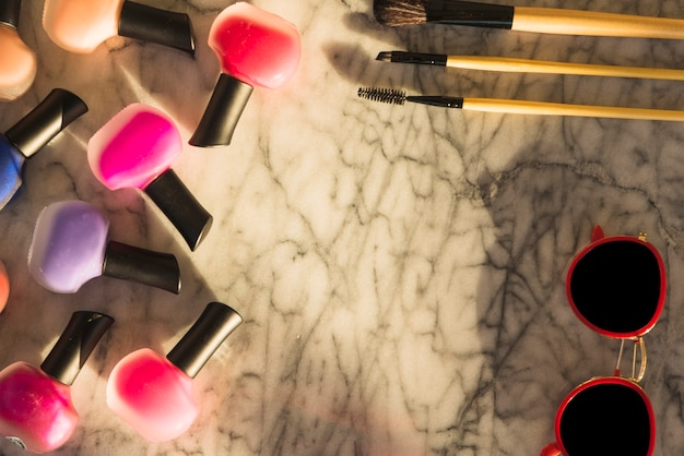 Variety of colorful lipsticks; brush; mascara; sunglasses over marble textured background Free Photo