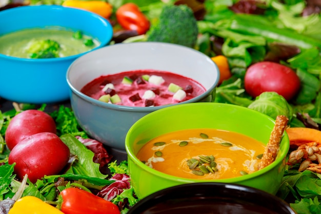 Variety of colorful tasty vegetables cream soups and fresh ingredients for soups. healthy food vegetarian food. Premium Photo