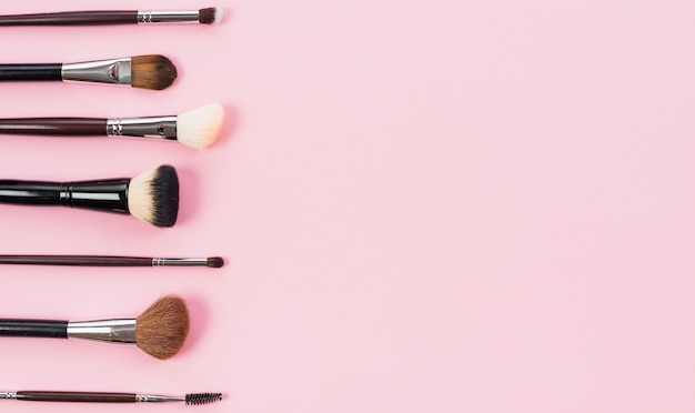 Variety of different makeup brushes on pink background Free Photo