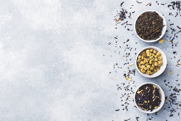 Variety Of Dry Tea Leaves And Flowers In Bowl On Grey Background Premium Photo