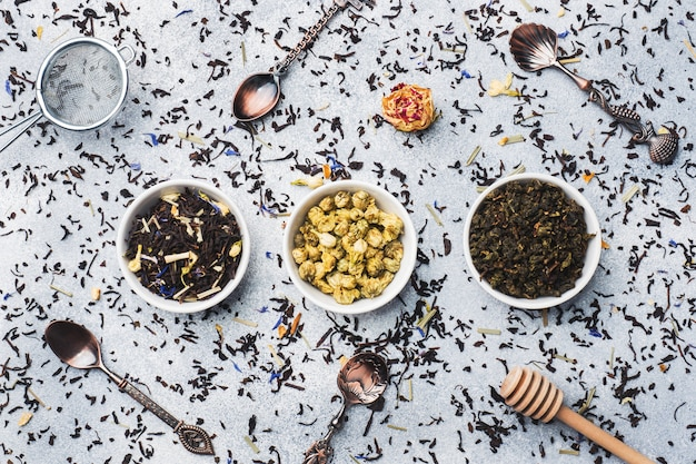 Variety of dry tea leaves and flowers in bowl on grey background. Premium Photo