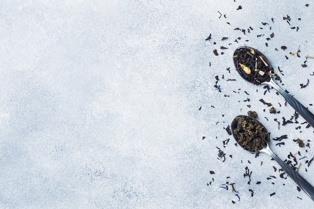 Variety of dry tea leaves and flowers in spoons on grey background copy space Premium Photo