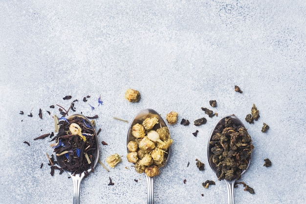 Variety of dry tea leaves and flowers in spoons on grey background Premium Photo