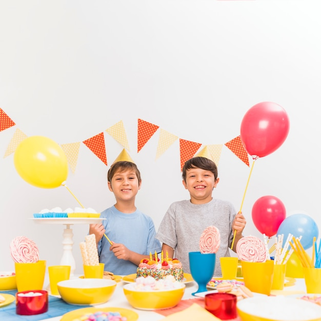 Variety of food on table with two boys holding balloons in party Free Photo