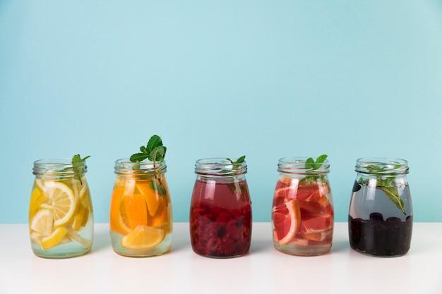 Varietà di succo di frutta fresca con sfondo azzurro Foto Gratuite