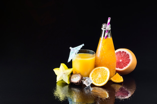 Variety of fruit and juices on black background Free Photo
