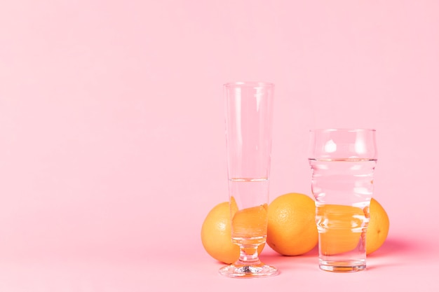 Variety of glasses filled with water and oranges Free Photo