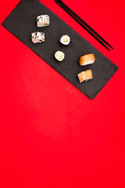 Variety of hot sushi rolls arranged on slate stone with chopsticks over colored background with space for text Free Photo