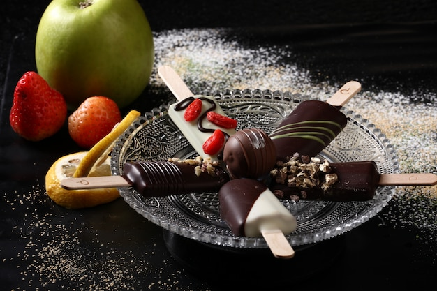 Variety of ice cream in the black wooden table. Premium Photo