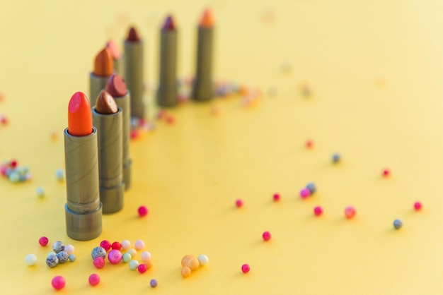 Variety of lipsticks shades arranged in row on yellow background Free Photo