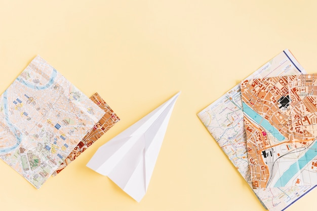 Variety of maps with white paper airplane on beige background Free Photo