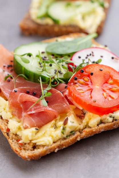 Variety of mini sandwiches with cream cheese, vegetables and salami. sandwiches with cucumber, radish, tomatoes, salami on a gray surface, top view. flat lay. Premium Photo