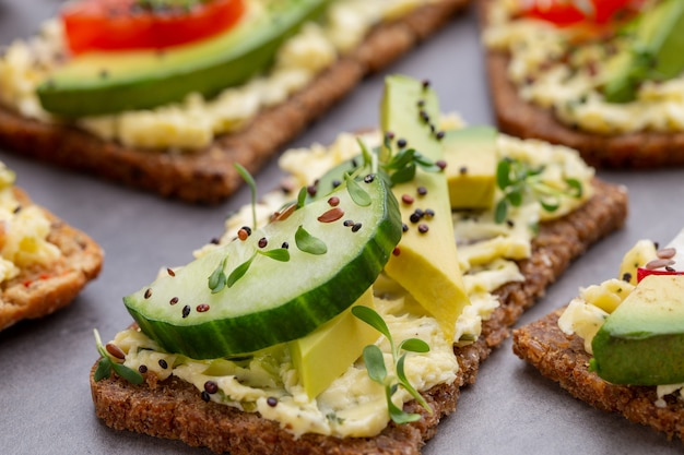 Variety of mini sandwiches with cream cheese, vegetables and salami. Premium Photo