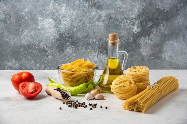 Разнообразие сырых макарон, бутылки оливкового масла, зерен перца и овощей на белом столе. Бесплатные Фотографии
