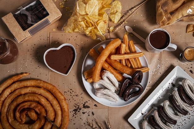 クラフ紙のテーブルにグラニュー糖とチョコレートを添えたさまざまな伝統的なチュロス。上面図。典型的なchurreria製品 Premium写真