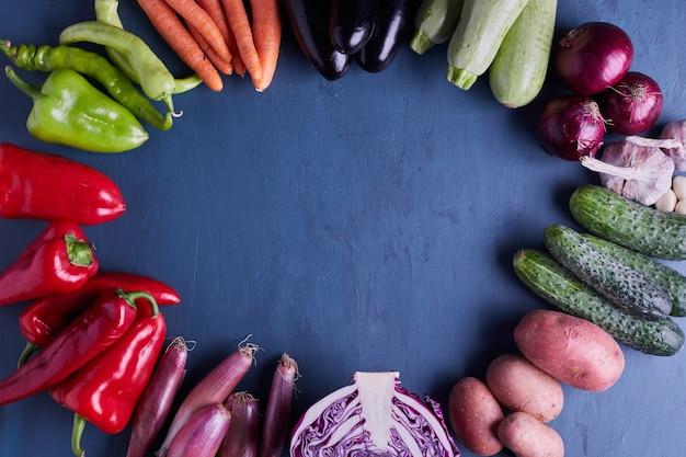 青いテーブルの上に輪になってさまざまな野菜。 無料写真